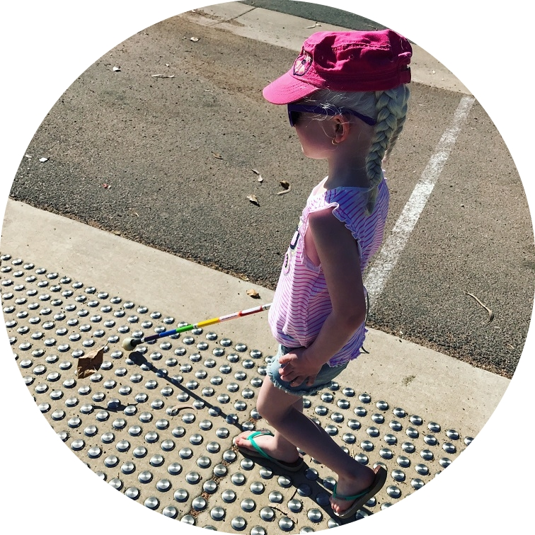 Image shows little girl walking down the street using her rainbow cane.