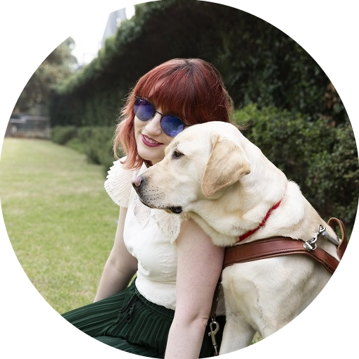 Image shows young girl resting her head on the head of her Guide Dog who is sitting next to her in a harness.